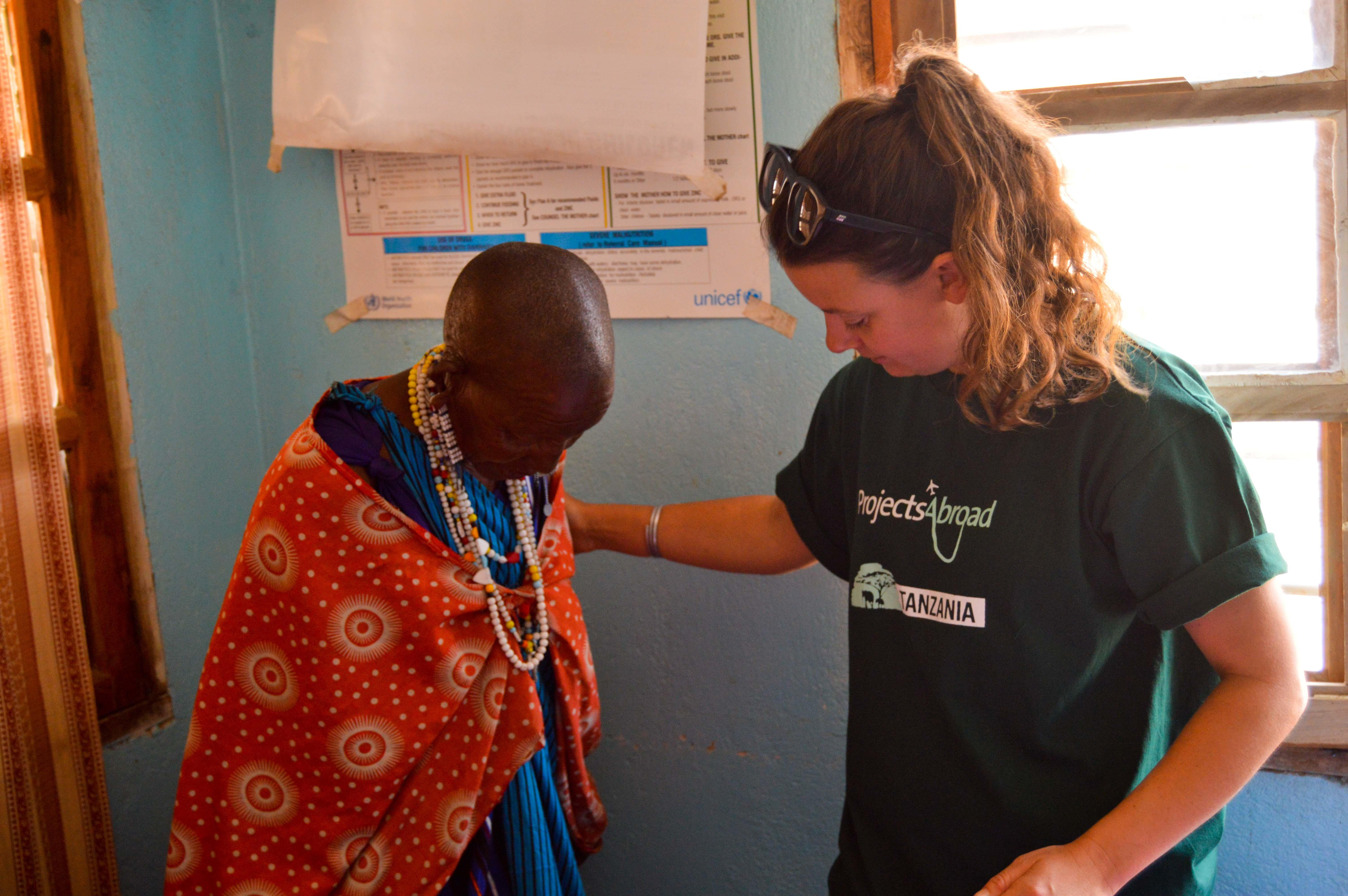 Female Projects Abroad intern is pictured assisting with weighing a Masai woman at the local clinic as part of her nursing internship in Tanzania.